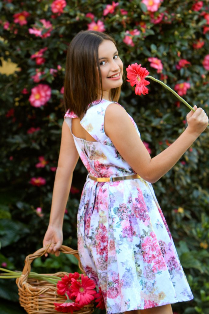 Young girl holding basket of flowers. Enjoy the skin you're in.